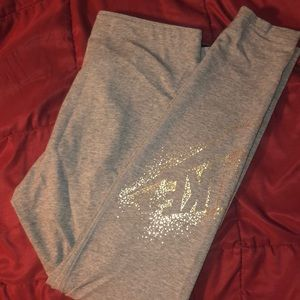 Gray Nike leggings with gold logo on calf